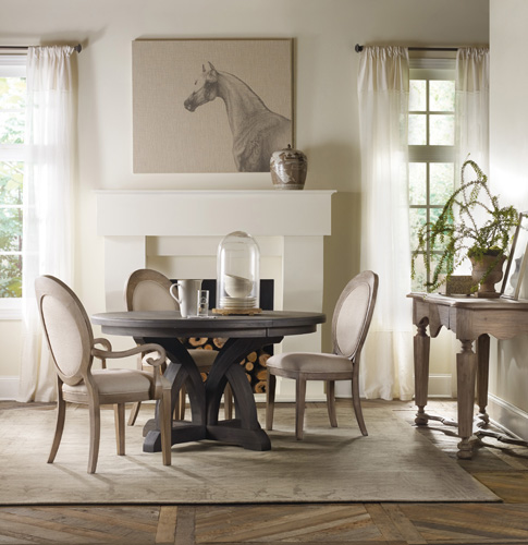 The 54-inch round Corsica dining table is in a dark espresso finish, while the chairs are in natural
