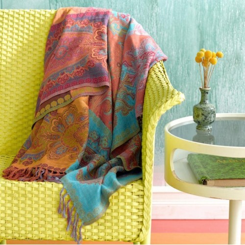 A yellow wicker settee isn't necessary to say 'spring' when you have vibrant flower hues like on this Aran throw from Pine Cone Hill. A few flowers in a vase add to the ambiance.