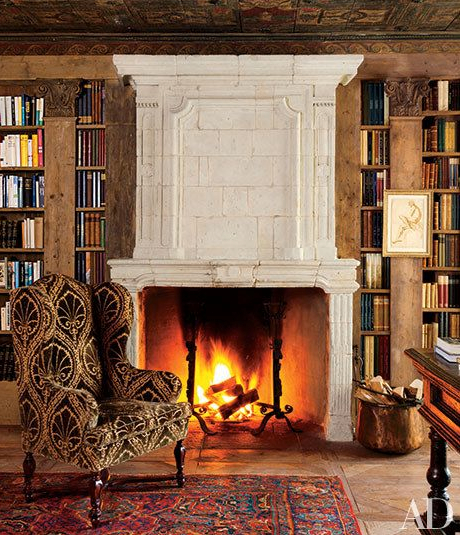 By nestling an antique wing chair next to a 17th century French fireplace mantel, the library in a Swiss Alps home is transformed into a cozy retreat. Photo: Oberto Gill, architecturaldigest.com
