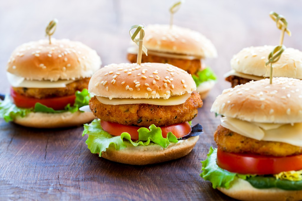 Appetizing mini chicken burgers on wooden surface.